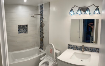 small modern bathroom with a white vanity, mirror and hardware.
